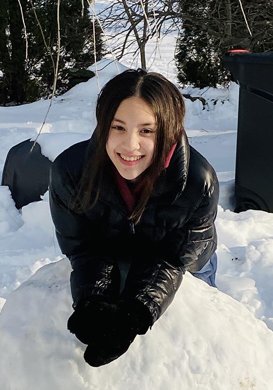 Mẫu nhí Lucy chơi đùa với tuyết trong khuôn viên vườn nhà tại Bắc Mỹ.
