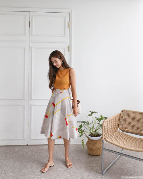Chân váy midi, áo lụa sát nách, sandal quai mảnh là phép cộng mang lại set đồ hợp mốt mùa nắng cho phái đẹp công sở.