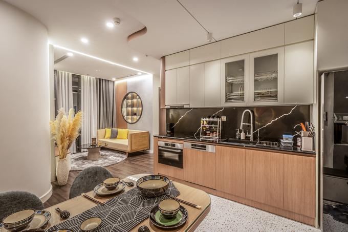 Phòng khách, bếp ăn được thiết kế theo không gian mở nhưng vẫn được xác định ranh giới rõ ràng nhờ cách sử dụng hai loại gạch, sàn gỗ họa tiết khác nhau.