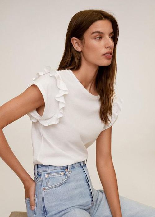 Áo cotton gam trắng quen thuộc trở nên mới mẻ hơn với chi tiết sát nách đi kèm bèo nhúng. Trang phục có thể kết hợp cùng quần jeans và các mẫu chân váy midi, quần âu.