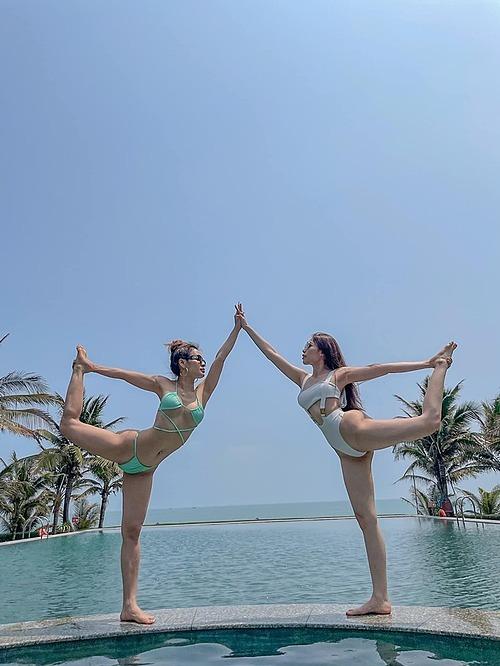 Phương Trinh Jolie (áo xanh) diện bikini tập yoga cùng bạn trên hồ bơi.