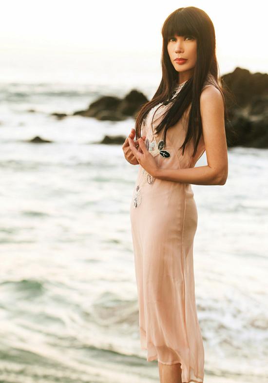 Nữ ca sĩ diện các thiết kế đơn giản, nữ tính, khoe vóc dáng thon thả khi diễn trước biển.