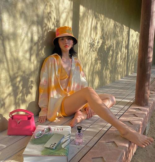 Khi đi du lịch và nghỉ dưỡng, Khánh Linh vẫn giữ thói quen mix-match trang phục và phụ kiện một cách chỉn chu. Túi Louis Vuitton được phối cùng sơ mi, mũ màu loang và đồ bơi tông vàng hot trend 2021/