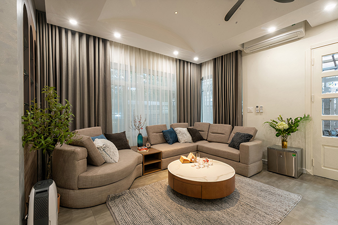 Với khoảng 2 tỷ đồng tiền cải tạo, thay thế nội thất, căn nhà đã được lột xác hoàn toàn. Gia chủ mong muốn các thành viên có thể quây quần bên nhau nhiều hơn, gắn kết tình cảm nên toàn bộ tầng trệt được dành cho những không gian sinh hoạt chung. Tầng trệt bao gồm phòng khách, bếp và khu vực ăn uống. Phòng khách có diện tích lớn, được bài trí gọn gàng với những gam màu trung tính làm chủ đạo, kết hợp với hệ tủ gỗ màu sáng mang lại cảm giác ấm cúng và sang trọng.
