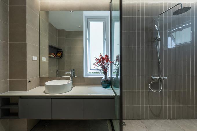 Phòng vệ sinh ngăn giữa bồn rửa tay và khu vực tắm, mang gam màu trung tính.