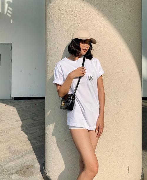 Diện nguyên set trang phục trắng tôn nét năng động, Tiểu Vy chọn túi đeo chéo tông màu tương phản để mix đồ.