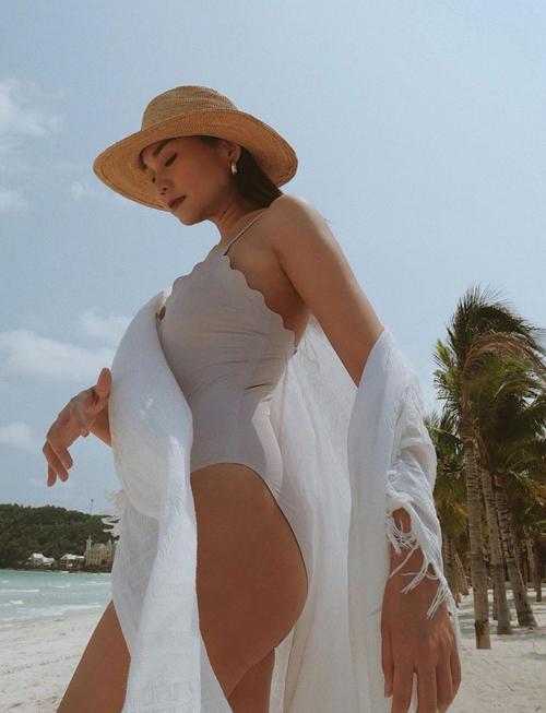 Đồ bơi với đường cắp cúp uốn lượn được chị đại làng mốt Việt phối đồng điệu với khăn choàng và mũ nan hợp mốt mùa hè.