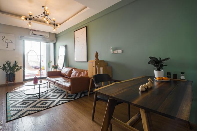 Phòng khách tiện nghi với sofa kết hợp bàn trà tròn hai tầng. Đèn chùm trên trần cũng mang phong cách hiện đại, không rườm rà.