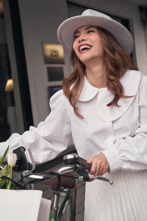 Khi diện váy midi trên chất liệu vải dập ly, Yến Trang chọn thêm áo sơ mi với thiết kế cổ sen biến tấu mang lại sự mới mẻ.
