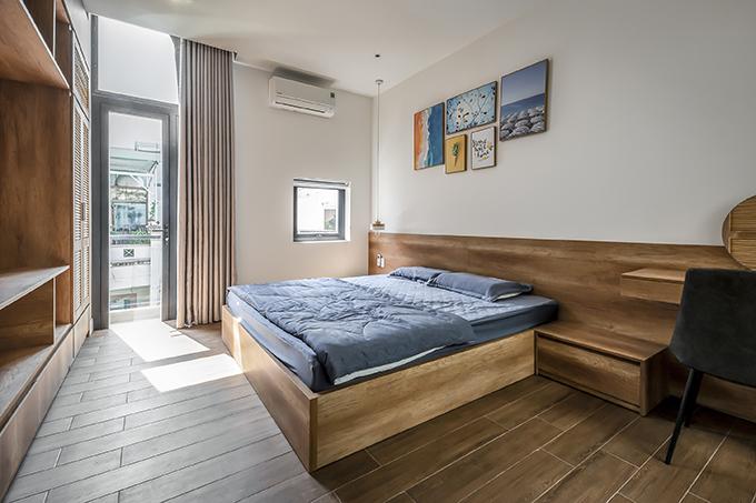 Phòng ngủ thứ hai có phong cách giống phòng ngủ đầu tiên và có thêm chi tiết tranh treo tường.