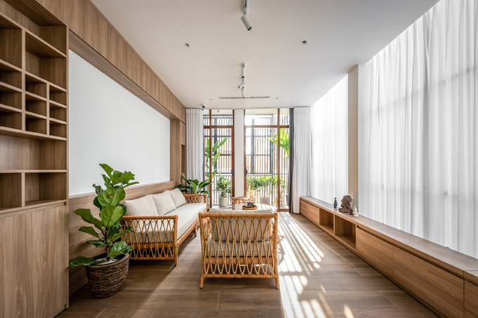 Phòng khách được đặt tại tầng 1 của ngôi nhà, có tông chủ đạo trắng - nâu gỗ. Căn phòng có mảng kính lớn, cây xanh xung quanh giúp giải phóng tầm nhìn, tạo sự thoải mái khi gia chủ sống trong nhà nhỏ.