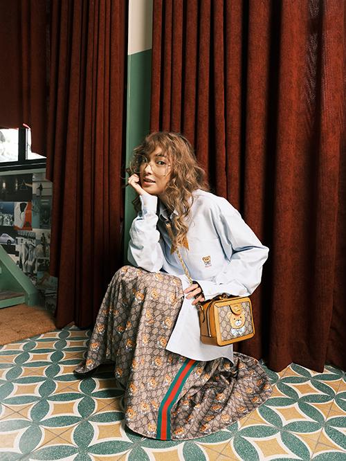Châu Bùi lăng xê triệt để với set đồ gồm áo sơ mi tay dài, chân váy midi và túi xách đều mang hoạ tiết gấu