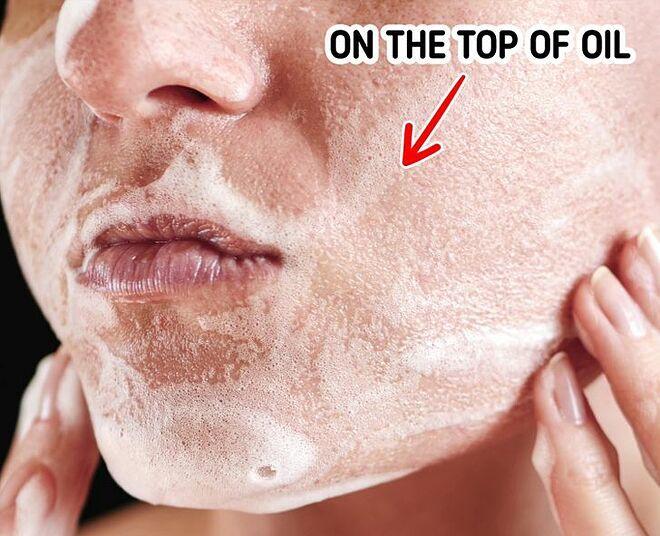 Thoa sữa rửa mặt dạng kem lên trên lớp dầu massage để làm sạch sâu.