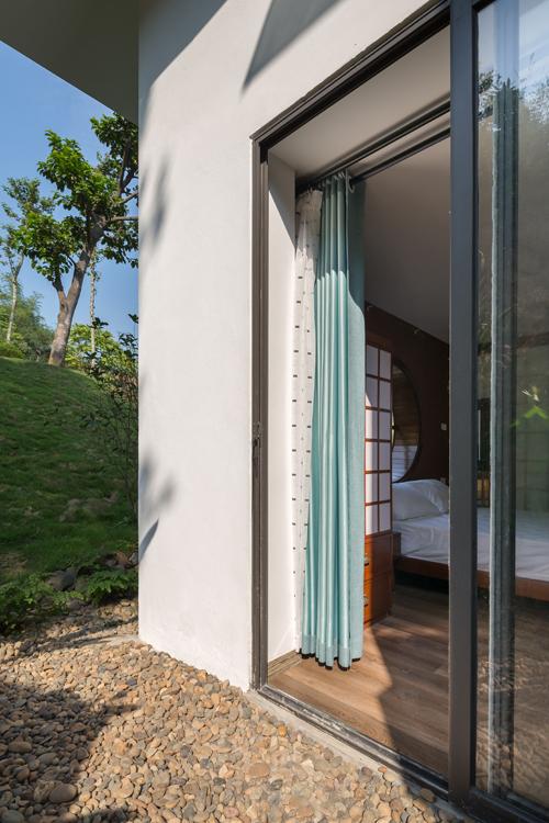 Ngoài lối cửa chính, chủ nhà có thể vào phòng ngủ nhờ cửa phụ. Nơi đây có thêm rèm để che nắng, giữ sự kín đáo cho căn phòng.