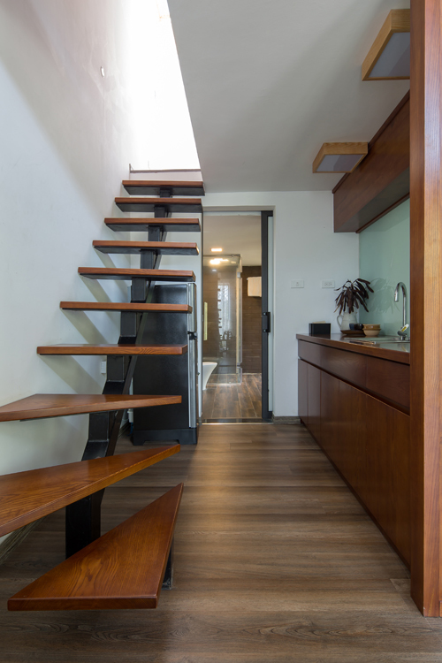 Khu vực bếp nấu nhỏ với đồ nội thất gỗ chủ đạo. Tủ lạnh được kê dưới chân cầu thang để tiết kiệm diện tích.
