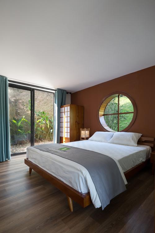 Phía bên trong phòng ngủ. Cửa sổ tròn được lựa chọn để đưa nắng, gió vào trong phòng ngủ.