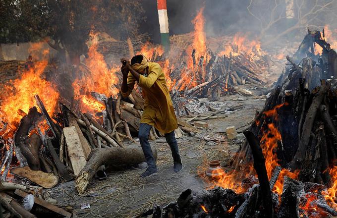 Một người đàn ông chạy qua bãi hỏa táng nơi thi thể một người thân của mình đang được đốt. Ảnh: Reuters.