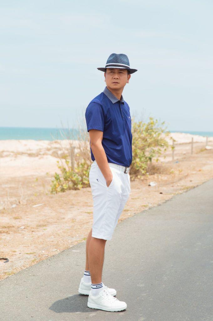 Nhạc sĩ kết hợp áo polo xanh biển phong cách hè với quần short trắng, đội mũ cùng tông. Set đồ giúp ông bố hai con trẻ, khỏe và lịch lãm.