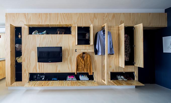 Để sắp xếp vật dụng của chủ nhà và khách, tường gỗ phòng khách cũng chính là hệ tủ có cửa, ngăn kéo được tạo ra để khi đóng lại, mọi người chỉ nhìn thấy tấm gỗ.