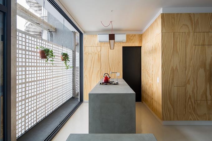 Cửa sắt cũ để ngăn căn hộ với mặt tiền toà nhà được thay thế bởi khung nhôm, có thể mở ra, kéo vào tạo sự lưu thông không khí trong căn hộ và giúp chủ nhà tận dụng được hành lang hẹp.