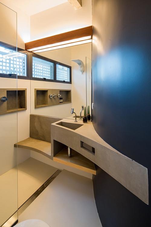 Phòng tắm có băng ghế bằng bê tông, có cấu trúc cong trùng với tường ngoài của căn hộ, khi chạm tới góc có vòi sen sẽ trở thành băng ghế hỗ trợ cho người dùng. Sơn epoxy được sử dụng trong phòng tắm để chủ nhà dễ làm sạch bề mặt khi dọn dẹp.
