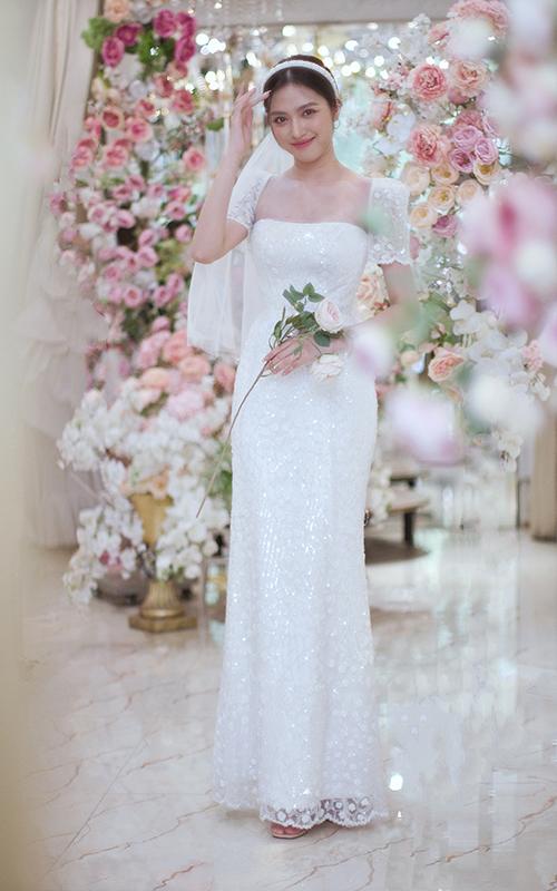 Đầm sheath được tạo độ bắt sáng tự nhiên nhờ chính chất liệu vải váy. Phần eo ôm để khoe trọn lợi thế thân hình của cô dâu, cổ vuông giúp tôn ngực đầy của tân nương.