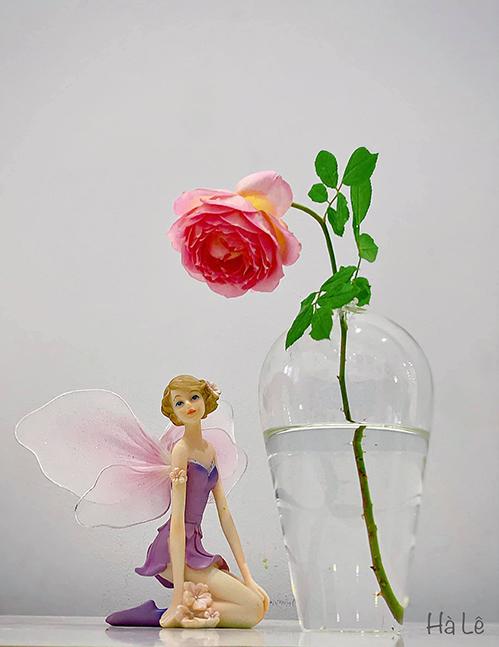 Chị cắm độc một bông trong bình thuỷ tinh trong suốt miệng nhỏ. Để không gian thêm đẹp, chị sử dụng tượng làm điểm nhấn trang trí cạnh bình hoa.