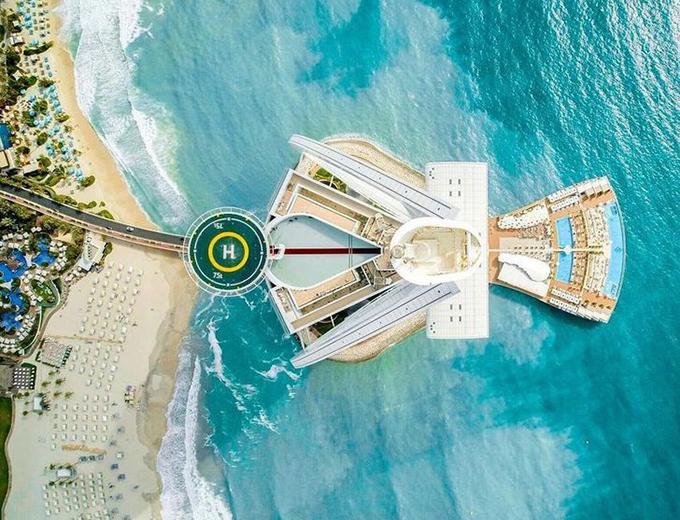 2. Xây dựng trên một hòn đảo nhân tạoKhách sạn được xây trên một hòn đảo nhân tạo hoàn toàn, nối với đất liền bằng một cây cầu chỉ mở cửa nhân viên và du khách nghỉ dưỡng. Toà nhà cao 300m, cao hơn cả tháp Eiffel gồm 56 tầng, 230 cột bê tông được chôn dưới biển để giữ phần móng được chắn chắn. Khách sạn được thiết kế hình cánh buồm, ngoài yếu tố thẩm mỹ, các kiến trúc sư muốn hạn chế ảnh hưởng của tia UV khi ánh nắng phản chiếu xuống người dưới bãi biển.
