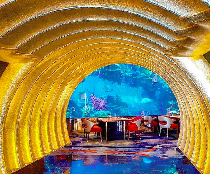 10. Nhà hàng phục vụ hải sản dưới nướcBurj Al Arab có một nhà hàng dưới nước tên là Al Mahara, tên gọi này có nghĩa là vỏ hàu. Lối vào nhà hàng là một hành lang có mái vòm màu vàng giống như một chiếc tàu ngầm. Ở trung tâm là một bể cá khổng lồ chứa đầy san hô đầy màu sắc và các loài cá kỳ lạ, bao gồm cả cá mập. Khách có thể thưởng thức bữa tối trong khi một con cá mập tình cờ bơi xung quanh. Bể cá thường dùng làm nơi cầu hôn với sự tham gia của thợ lặn.
