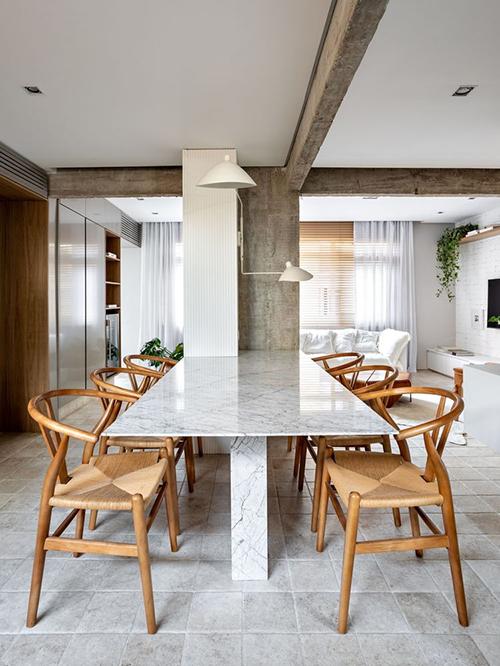 Nơi bàn ăn làm bằng đá cẩm thạch carrara, thẳng hàng với cột bê tông.