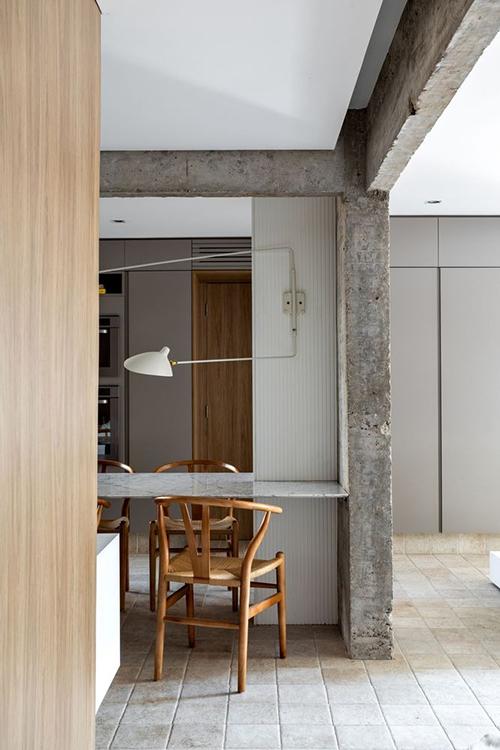 Cột trung tâm giữa bếp và phòng khách không thể phá bỏ. Vì thế, giải pháp thiết kế được đưa ra là bóc trần, để lộ kết cấu bê tông. Hầu hết các tường ngăn đã bị phá bỏ, cho phép phân bổ, quy hoạch lại vị trí các phòng chức năng.