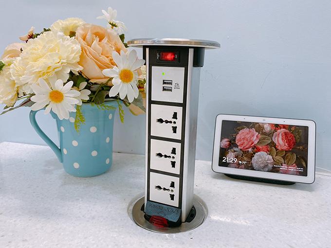 Ổ điện kiêm cổng cắm USB để sạc điện thoại do chồng chị Hằng thực hiện. Khi không sử dụng, chị chỉ việc nhấn để đẩy ổ điện xuống mặt bàn.