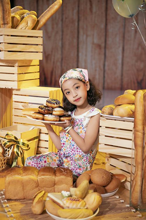 Thí sinh Mina chọn trang phục và khăn đồng điệu sắc màu khi hoá thân thành cô bé làm bánh xinh xắn.