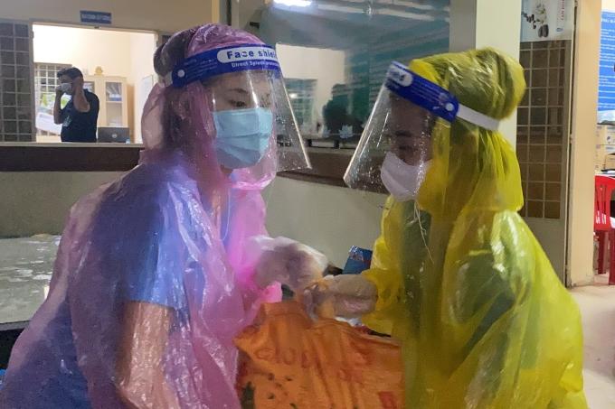 Các cô gái cố gắng chuyền tay nhau từng bao gạo nặng từ xe vào điểm tập kết. Dưới mưa lớn, họ tập trung làm việc để lương thực, thực phẩm sớm được đến tay bà con lao động.