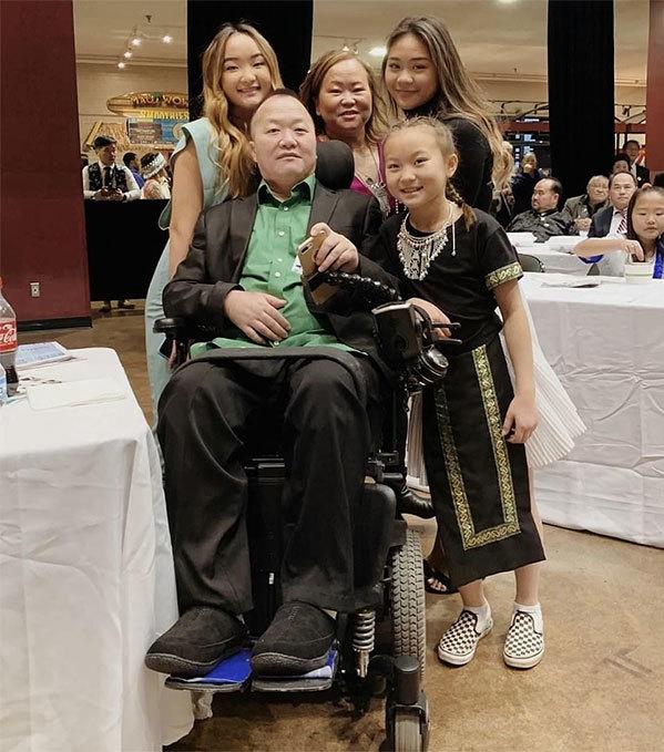 Sunisa (đứng sau ngoài cùng bên phải) bên bố mẹ và các chị em gái. Lúc này bố cô vừa gặp tai nạn, phải ngồi xe lăn. Ảnh: Twitter.