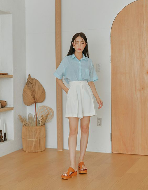 Set đồ phù hợp với không khí giao mùa với cách phối sơ mi chất liệu mỏng đi cùng short trắng vải linen, vải bố mỏng và sandal đế thô.